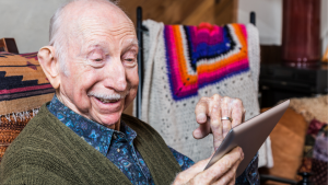 Elderly man on a tablet appearing to be watching/speaking to someone.