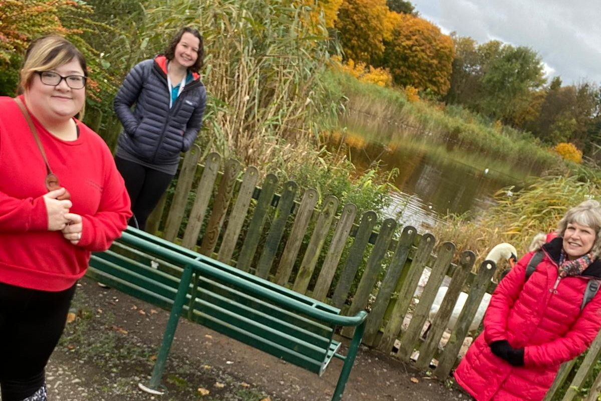 Picture of support workers Jamie, Karin and Alison by pond.