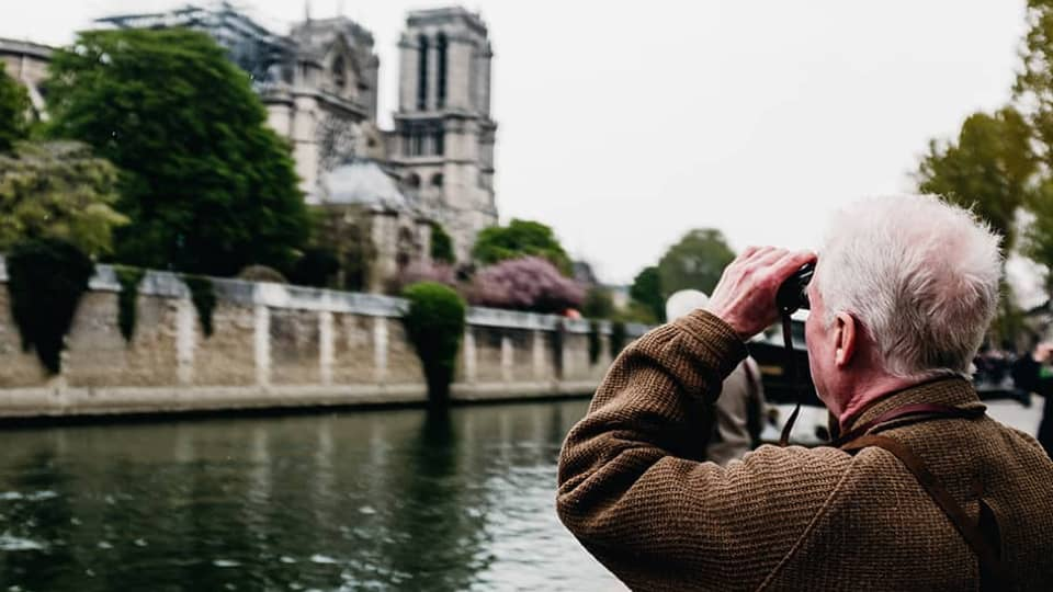 Older man looking into binoculars looking across a river/canal.