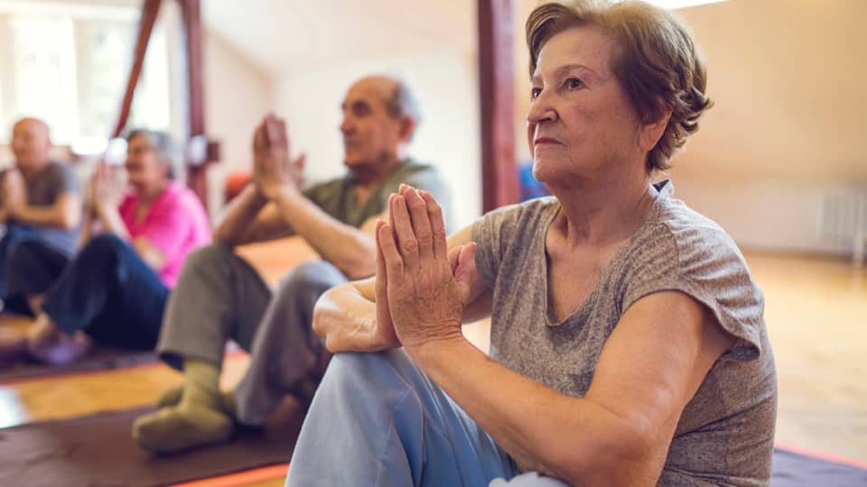 Group with older people in a yoga class.