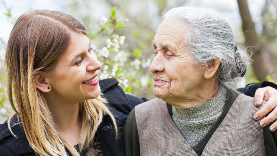 Photo of a young lady with an arm around an older woman. Both are looking and smiling at each other.