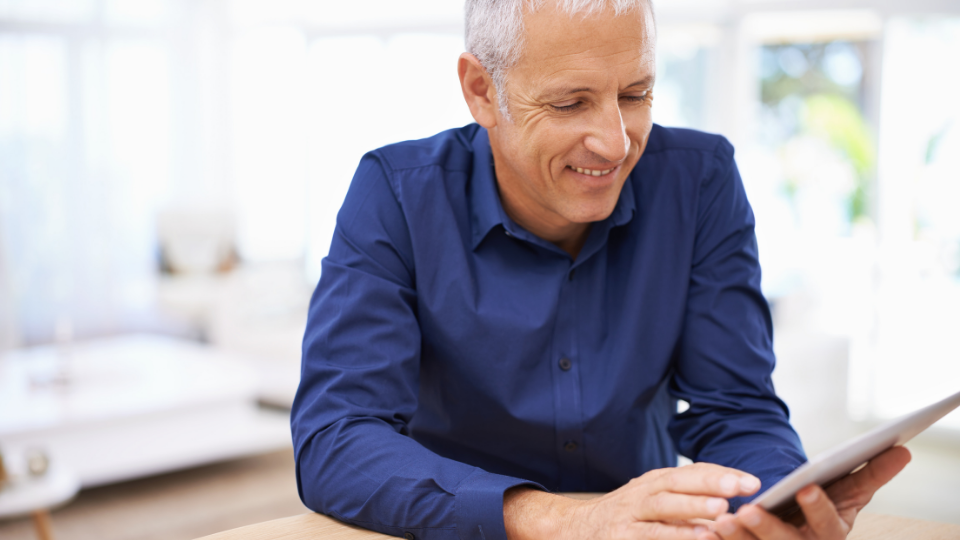 Older man smiling down at a tablet device