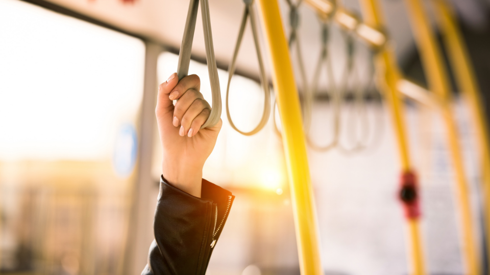 Image of hand holding a standing only strap inside a bus.