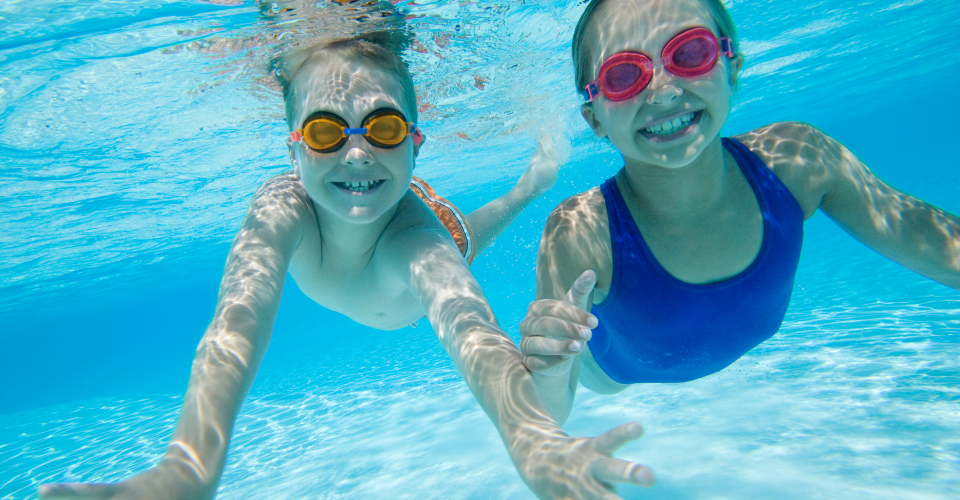 An underwater shot of a young boy and girl swimming.