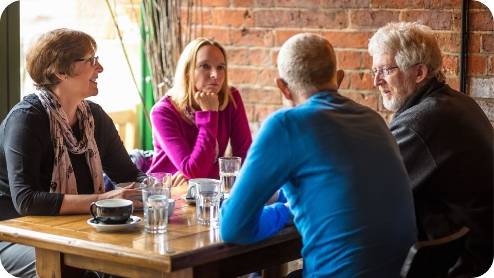 Group of four people sitting round a table chatting