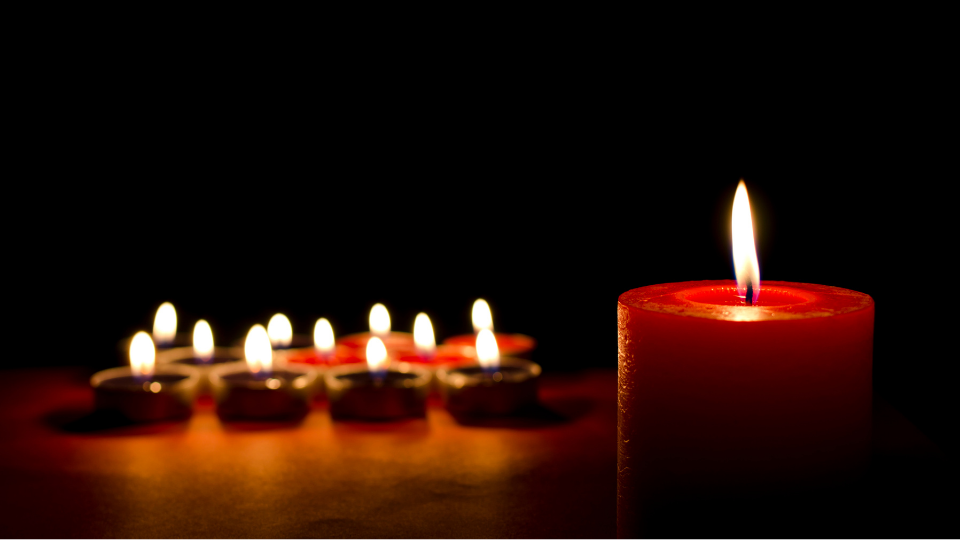Image of large red candle that is alight against a dark backdrop. In the background there are eight lit tealights.