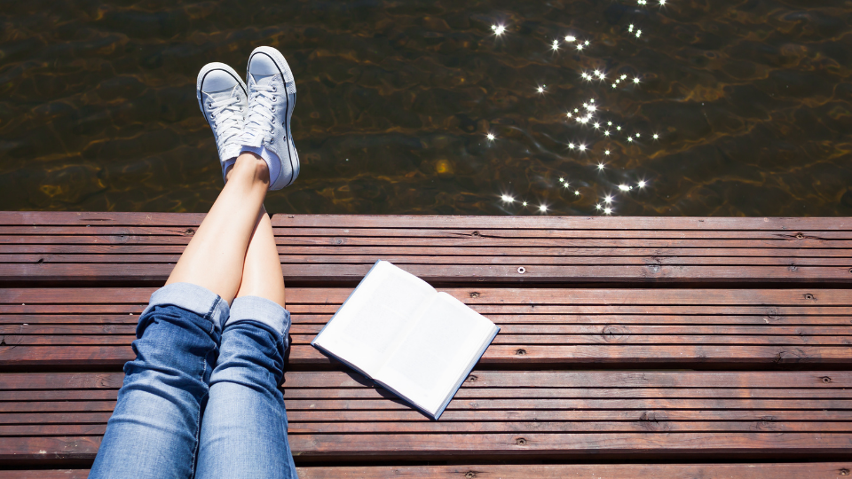 Downward shot of a ledge of a wooden lake deck , a pair of crossed legs are in shot with an open book beside them..