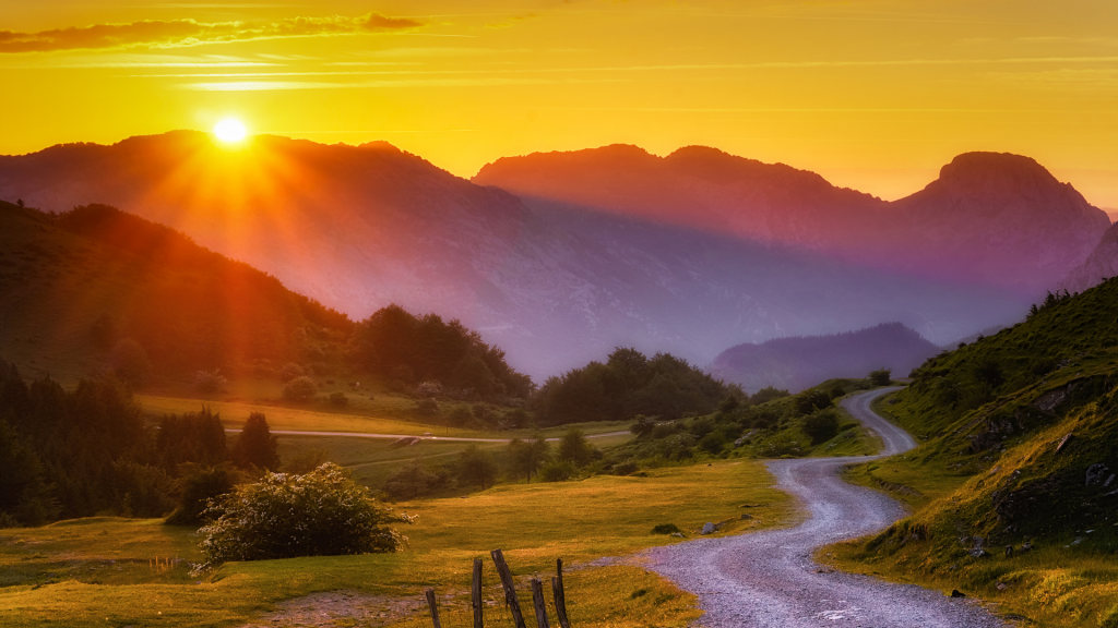 Image of a sunset against a range of mountains. In the foreground there is a curving road leading to the mountains.